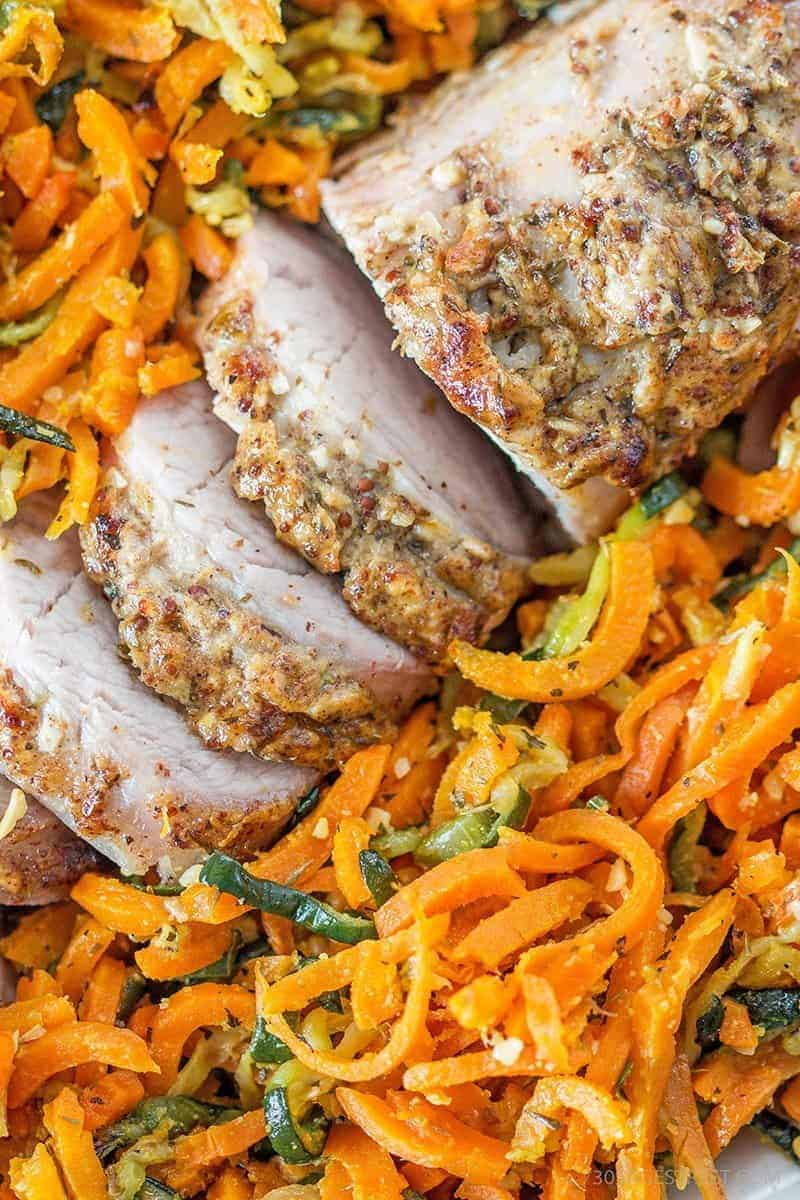 close up of a pork tenderloin sitting on a bed of spiral carrots