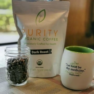 small jar filled with purity dark roast coffee beans (left), 12 oz bag of purity dark roast (center), and new purity coffee mug (right)