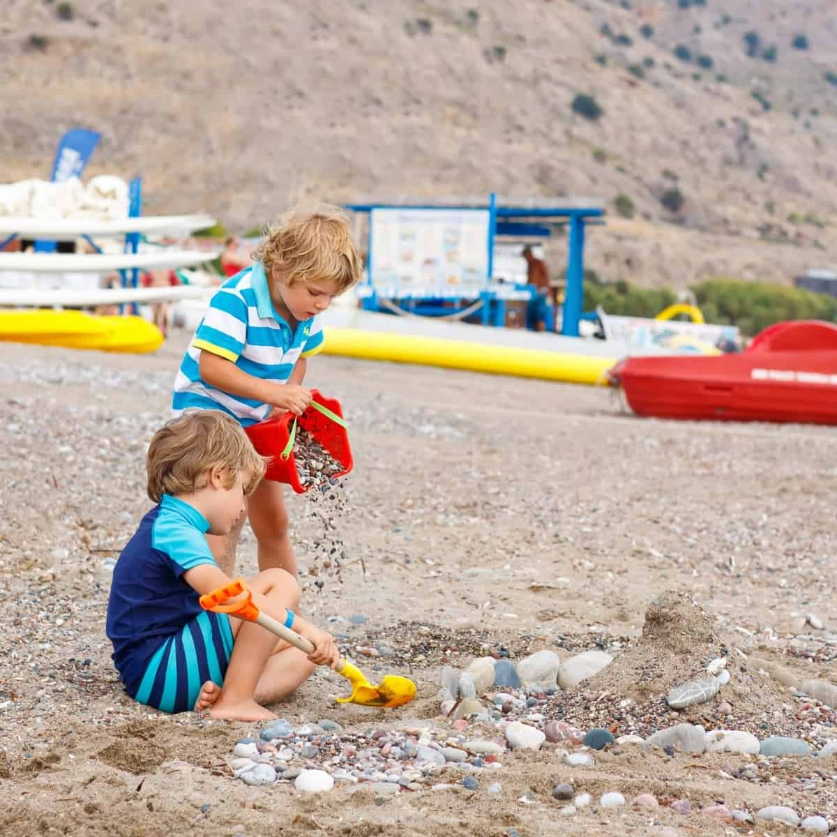 kids playing with sand at the beach