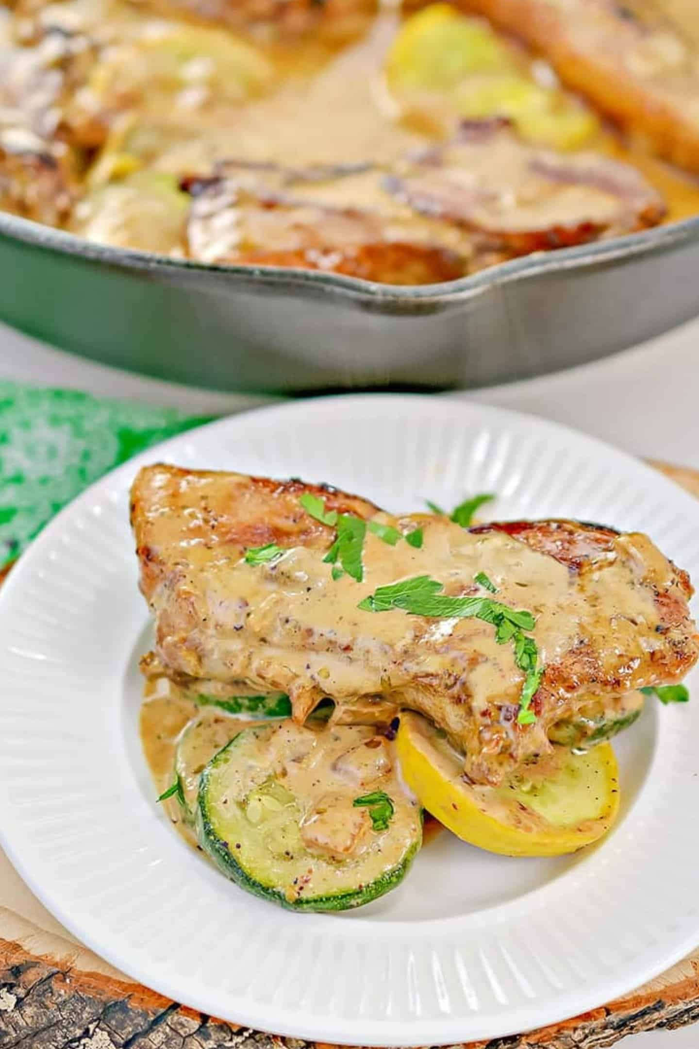 pan seared thin pork chops on white plate covered in creamy mustard sauce