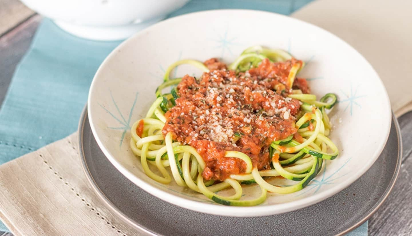 zucchini pasta noodles with marinara and cheese on top